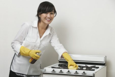 smiling Chinese cleaner is cleaning white stove with cleaning materials